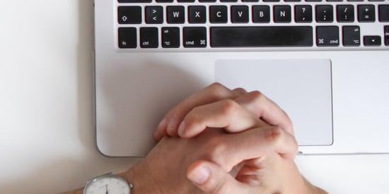 hands resting on laptop keyboard